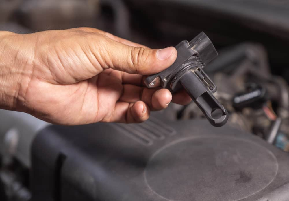 Check air flow meter automobile engine by car technician.