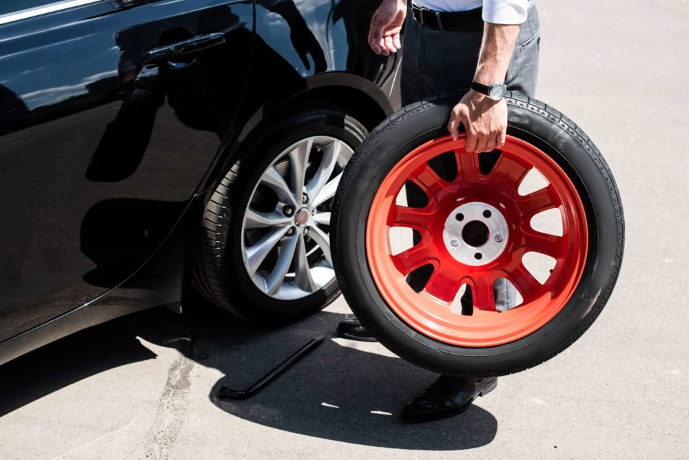 Cropped image of businessman holding tire for wheel replacement at street .