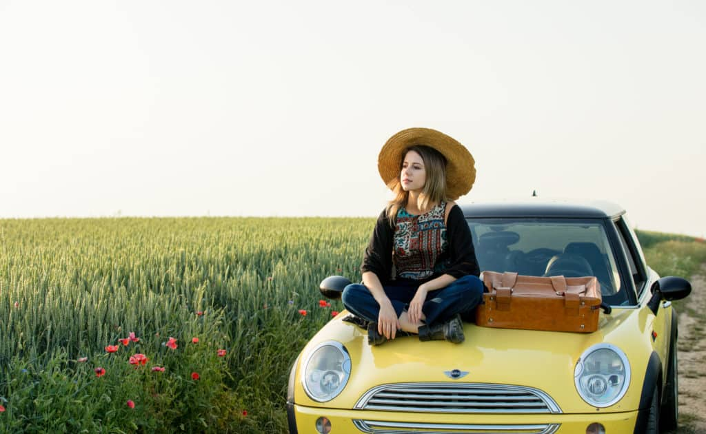 Wroclaw, Poland - 11 June 2019 - woman with suitcase sitting on yellow Mini Cooper R50 on countryside road between wheat fields in sunset time.