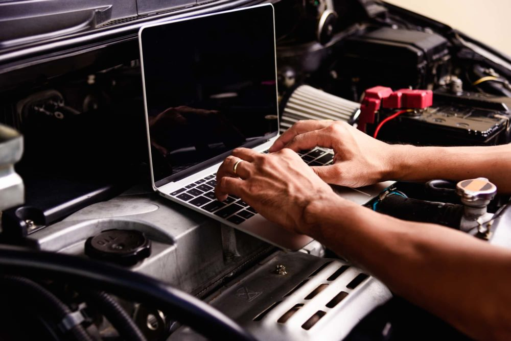 Professional car repair or maintenance mechanic engine working service with laptop computer at workshop