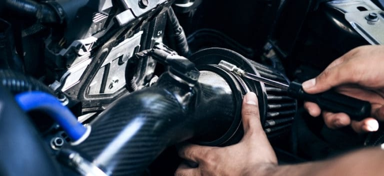 Man's hand working on car's engine with tool on his hand