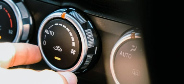 Man's hand holding one of car's switch or button